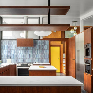 Photo of a midcentury kitchen in Atlanta with a drop-in sink, flat-panel cabinets, dark wood cabinets, blue splashback, ceramic splashback, stainless steel appliances, grey floor, white benchtop and slate floors.