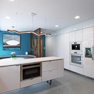 Modelo de cocina comedor en L, retro, de tamaño medio, con fregadero bajoencimera, armarios con paneles lisos, puertas de armario blancas, encimera de cuarcita, salpicadero blanco, electrodomésticos blancos, suelo de terrazo, una isla, suelo gris y encimeras blancas