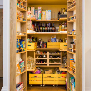 Große Klassische Küche in L-Form mit integriertem Waschbecken, flächenbündigen Schrankfronten, gelben Schränken, Quarzwerkstein-Arbeitsplatte, Küchengeräten aus Edelstahl, Porzellan-Bodenfliesen, Kücheninsel, braunem Boden und Vorratsschrank in Manchester