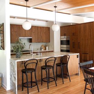 デトロイトのミッドセンチュリースタイルのおしゃれなアイランドキッチン (フラットパネル扉のキャビネット、中間色木目調キャビネット、珪岩カウンター、グレーのキッチンパネル、ガラスタイルのキッチンパネル、シルバーの調理設備の、無垢フローリング、茶色い床、ベージュのキッチンカウンター) の写真