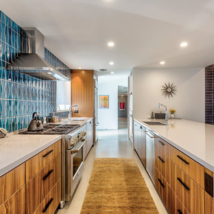 Midcentury modern eat-in kitchen pictures - Inspiration for a 1960s galley concrete floor and gray floor eat-in kitchen remodel in Phoenix with an undermount sink, flat-panel cabinets, medium tone wood cabinets, quartz countertops, blue backsplash, ceramic backsplash, stainless steel appliances and a peninsula
