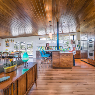 Photo of a midcentury kitchen in Denver with a drop-in sink, flat-panel cabinets, white cabinets, granite benchtops, multi-coloured splashback, ceramic splashback, stainless steel appliances, light hardwood floors, with island and turquoise benchtop.