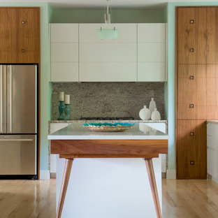 Photo of a mid-sized midcentury single-wall eat-in kitchen in Atlanta with flat-panel cabinets, medium wood cabinets, solid surface benchtops, beige splashback, stone slab splashback, stainless steel appliances, light hardwood floors and with island.