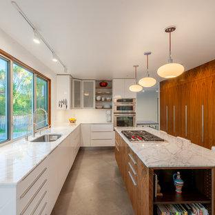 Bild på ett mellanstort 50 tals kök, med en undermonterad diskho, släta luckor, vita skåp, marmorbänkskiva, rostfria vitvaror, cementgolv och en köksö
