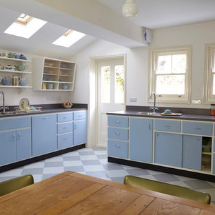 Design ideas for a mid-sized midcentury l-shaped eat-in kitchen in London with a double-bowl sink, flat-panel cabinets, laminate benchtops, grey splashback, panelled appliances, linoleum floors, no island, multi-coloured floor and grey benchtop.