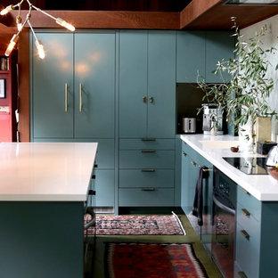 Aménagement d'une cuisine américaine parallèle classique de taille moyenne avec un évier intégré, un placard à porte plane, des portes de placards vertess, un plan de travail en granite, une crédence verte, béton au sol, un îlot central et un sol vert.