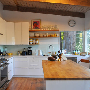 Inspiration for a mid-sized modern l-shaped dark wood floor open concept kitchen remodel in San Francisco with stainless steel appliances, glass sheet backsplash, an undermount sink, flat-panel cabinets, medium tone wood cabinets, quartz countertops, white backsplash and an island