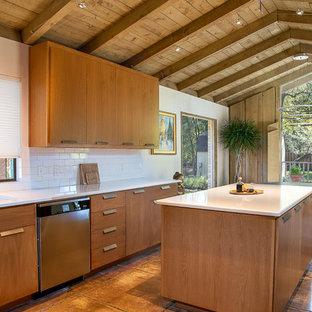 Foto på ett 60 tals vit kök och matrum, med en undermonterad diskho, släta luckor, skåp i mellenmörkt trä, vitt stänkskydd, stänkskydd i tunnelbanekakel, rostfria vitvaror, en köksö och brunt golv