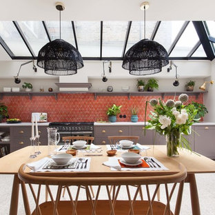 Expansive transitional eat-in kitchen in London with a farmhouse sink, shaker cabinets, grey cabinets, red splashback, black appliances, no island, grey floor, white benchtop, quartzite benchtops, cement tile splashback and terrazzo floors.