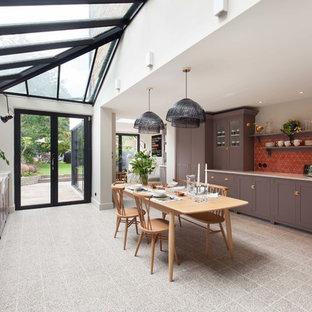 ロンドンの巨大なミッドセンチュリースタイルのおしゃれなダイニングキッチン (エプロンフロントシンク、シェーカースタイル扉のキャビネット、紫のキャビネット、珪岩カウンター、赤いキッチンパネル、セメントタイルのキッチンパネル、黒い調理設備、テラゾの床、アイランドなし、グレーの床、白いキッチンカウンター) の写真