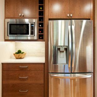 ナッシュビルの中サイズのミッドセンチュリースタイルのおしゃれなキッチン (アンダーカウンターシンク、フラットパネル扉のキャビネット、中間色木目調キャビネット、クオーツストーンカウンター、ベージュキッチンパネル、モザイクタイルのキッチンパネル、シルバーの調理設備の、淡色無垢フローリング、茶色い床、ベージュのキッチンカウンター) の写真
