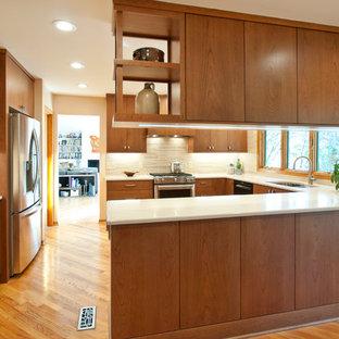 ナッシュビルの中くらいのミッドセンチュリースタイルのおしゃれなキッチン (アンダーカウンターシンク、フラットパネル扉のキャビネット、中間色木目調キャビネット、クオーツストーンカウンター、ベージュキッチンパネル、モザイクタイルのキッチンパネル、シルバーの調理設備、淡色無垢フローリング、茶色い床、ベージュのキッチンカウンター) の写真