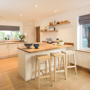 Einzeilige, Mittelgroße Moderne Wohnküche mit weißen Schränken, Arbeitsplatte aus Holz, braunem Holzboden, Halbinsel, Einbauwaschbecken, Lamellenschränken und Küchenrückwand in Weiß in Cambridgeshire