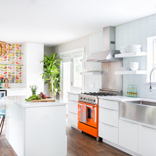 Photo of a medium sized retro single-wall kitchen/diner in Austin with a belfast sink, flat-panel cabinets, white cabinets, engineered stone countertops, white splashback, glass tiled splashback, stainless steel appliances, ceramic flooring and an island.