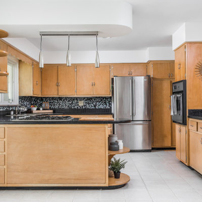 Inspiration for a mid-century modern u-shaped gray floor kitchen remodel in Indianapolis with a drop-in sink, flat-panel cabinets, medium tone wood cabinets, multicolored backsplash, mosaic tile backsplash, stainless steel appliances, a peninsula and black countertops