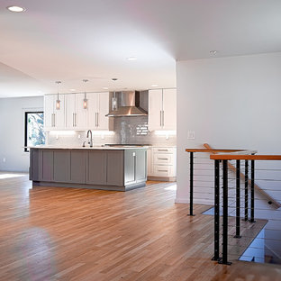 Mid-sized modern eat-in kitchen inspiration - Eat-in kitchen - mid-sized modern single-wall light wood floor and brown floor eat-in kitchen idea in Other with an undermount sink, shaker cabinets, white cabinets, quartzite countertops, gray backsplash, subway tile backsplash, stainless steel appliances, an island and white countertops