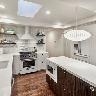 This is an example of a mid-sized midcentury u-shaped open plan kitchen in San Francisco with an undermount sink, flat-panel cabinets, white cabinets, white splashback, white appliances, dark hardwood floors, with island, brown floor and quartzite benchtops.