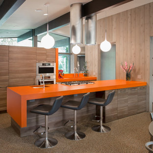 Mid-century modern eat-in kitchen remodeling - Example of a mid-century modern galley eat-in kitchen design in Austin with an undermount sink, flat-panel cabinets, light wood cabinets, laminate countertops, stainless steel appliances and orange countertops