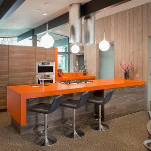 Cette image montre une cuisine américaine parallèle vintage avec un évier encastré, un placard à porte plane, des portes de placard en bois clair, un plan de travail en stratifié, un électroménager en acier inoxydable et un plan de travail orange.