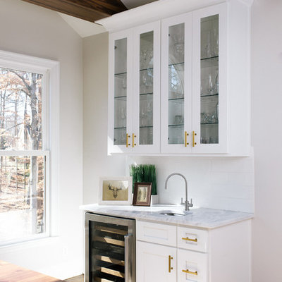 Eat-in kitchen - large transitional l-shaped dark wood floor eat-in kitchen idea in Atlanta with a farmhouse sink, shaker cabinets, white cabinets, marble countertops, white backsplash, ceramic backsplash, stainless steel appliances and an island