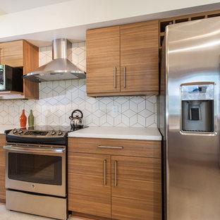 ミネアポリスの中サイズのコンテンポラリースタイルのおしゃれなキッチン (フラットパネル扉のキャビネット、中間色木目調キャビネット、人工大理石カウンター、白いキッチンパネル、セラミックタイルのキッチンパネル、シルバーの調理設備の、クッションフロア) の写真