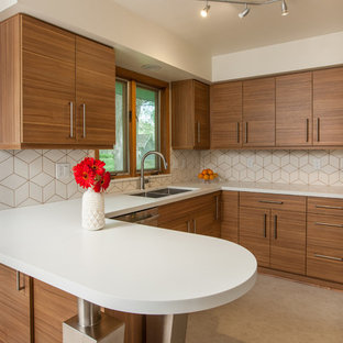 Mid-sized contemporary u-shaped eat-in kitchen in Minneapolis with an undermount sink, flat-panel cabinets, medium wood cabinets, solid surface benchtops, white splashback, ceramic splashback, stainless steel appliances, vinyl floors and a peninsula.