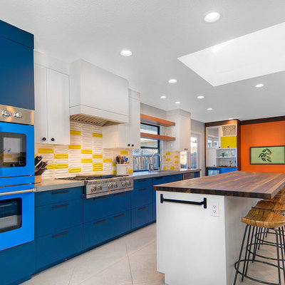 Example of a trendy galley ceramic tile and white floor eat-in kitchen design in San Francisco with an undermount sink, flat-panel cabinets, blue cabinets, quartz countertops, yellow backsplash, ceramic backsplash, colored appliances, an island and gray countertops
