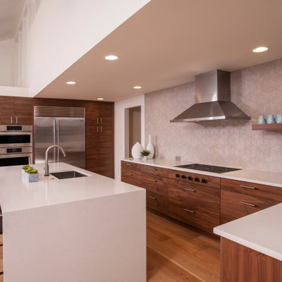 Example of a large 1960s u-shaped medium tone wood floor and brown floor open concept kitchen design in Seattle with an integrated sink, flat-panel cabinets, dark wood cabinets, quartzite countertops, gray backsplash, porcelain backsplash, stainless steel appliances, an island and white countertops