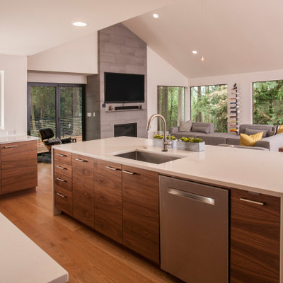 Example of a large mid-century modern u-shaped medium tone wood floor and brown floor open concept kitchen design in Seattle with an integrated sink, flat-panel cabinets, dark wood cabinets, quartzite countertops, gray backsplash, porcelain backsplash, stainless steel appliances, an island and white countertops