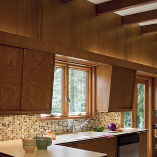 Mid-sized midcentury u-shaped separate kitchen in Portland with flat-panel cabinets, medium wood cabinets, laminate benchtops, multi-coloured splashback, stainless steel appliances, carpet and no island.