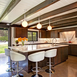 Photo of a midcentury l-shaped kitchen in San Diego with an undermount sink, flat-panel cabinets, dark wood cabinets, concrete floors and with island.
