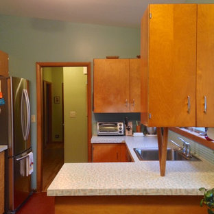 Design ideas for a mid-sized midcentury u-shaped kitchen in Seattle with a single-bowl sink, flat-panel cabinets, light wood cabinets, laminate benchtops, blue splashback, ceramic splashback, stainless steel appliances, linoleum floors and a peninsula.