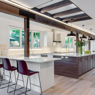 Photo of an expansive midcentury galley open plan kitchen in Portland with an undermount sink, flat-panel cabinets, white cabinets, quartz benchtops, white splashback, limestone splashback, stainless steel appliances, light hardwood floors, with island, brown floor and white benchtop.