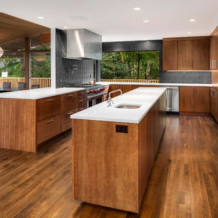 Inspiration for a large midcentury u-shaped open plan kitchen in Seattle with an undermount sink, flat-panel cabinets, light wood cabinets, quartz benchtops, black splashback, cement tile splashback, stainless steel appliances, medium hardwood floors and with island.