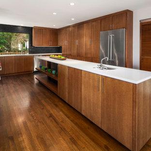 シアトルの大きいミッドセンチュリースタイルのおしゃれなアイランドキッチン (アンダーカウンターシンク、フラットパネル扉のキャビネット、クオーツストーンカウンター、黒いキッチンパネル、セメントタイルのキッチンパネル、シルバーの調理設備、無垢フローリング、中間色木目調キャビネット、茶色い床) の写真