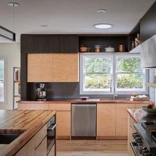 Mittelgroße Mid-Century Wohnküche in U-Form mit Landhausspüle, flächenbündigen Schrankfronten, hellen Holzschränken, Kupfer-Arbeitsplatte, Küchenrückwand in Grau, Küchengeräten aus Edelstahl, hellem Holzboden, Halbinsel, braunem Boden und brauner Arbeitsplatte in Atlanta