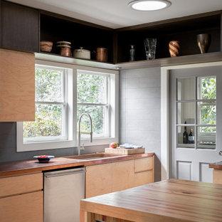 Inredning av ett retro mellanstort brun brunt kök, med en rustik diskho, släta luckor, skåp i ljust trä, bänkskiva i akrylsten, grått stänkskydd, rostfria vitvaror, ljust trägolv, en halv köksö och brunt golv
