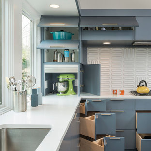 Mid-century modern u-shaped dark wood floor kitchen photo in Boston with an undermount sink, white backsplash, flat-panel cabinets, quartzite countertops, ceramic backsplash, stainless steel appliances and blue cabinets