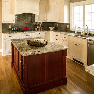 Eat-in kitchen - mid-sized transitional u-shaped medium tone wood floor eat-in kitchen idea in Providence with recessed-panel cabinets, white cabinets, granite countertops, gray backsplash, glass tile backsplash, stainless steel appliances and an island
