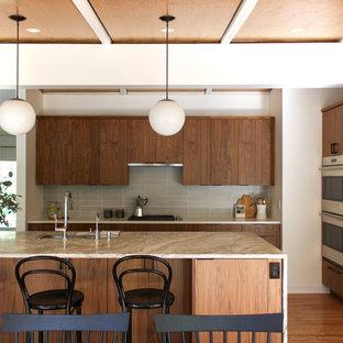 デトロイトのミッドセンチュリースタイルのおしゃれなキッチン (アンダーカウンターシンク、フラットパネル扉のキャビネット、中間色木目調キャビネット、グレーのキッチンパネル、パネルと同色の調理設備、無垢フローリング、茶色い床、ベージュのキッチンカウンター) の写真