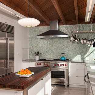 This is an example of a midcentury kitchen in San Diego with an undermount sink, flat-panel cabinets, white cabinets, multi-coloured splashback, mosaic tile splashback, stainless steel appliances, with island, marble benchtops and marble floors.
