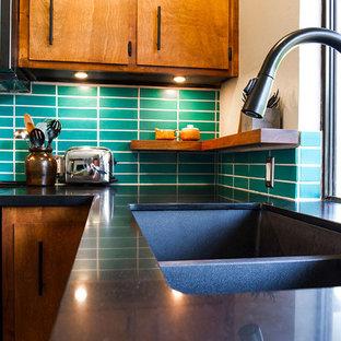 Foto på ett 50 tals kök, med skåp i mörkt trä, grönt stänkskydd, stänkskydd i keramik och en köksö