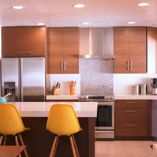 This is an example of a mid-sized midcentury u-shaped eat-in kitchen in Phoenix with flat-panel cabinets, quartz benchtops, stainless steel appliances, with island, medium wood cabinets, white splashback, an undermount sink, subway tile splashback and ceramic floors.