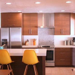 Inspiration pour une cuisine américaine vintage en U de taille moyenne avec un placard à porte plane, un plan de travail en quartz modifié, un électroménager en acier inoxydable, un îlot central, des portes de placard en bois brun, une crédence blanche, un évier encastré, une crédence en carrelage métro et un sol en carrelage de céramique.