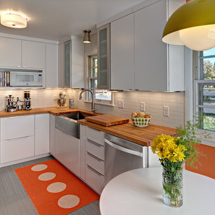Design ideas for a small midcentury u-shaped eat-in kitchen in Minneapolis with a farmhouse sink, flat-panel cabinets, white cabinets, wood benchtops, white splashback, ceramic splashback, linoleum floors, no island and stainless steel appliances.