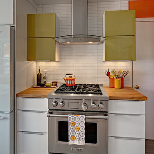 Design ideas for a small midcentury u-shaped separate kitchen in Minneapolis with a farmhouse sink, flat-panel cabinets, white cabinets, wood benchtops, white splashback, ceramic splashback, stainless steel appliances, linoleum floors and no island.