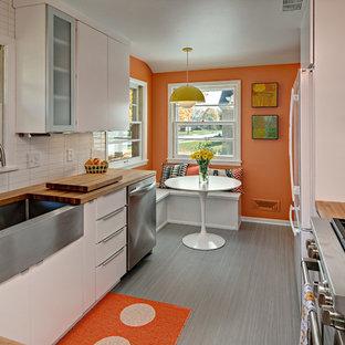 ミネアポリスのミッドセンチュリースタイルのおしゃれなキッチン (エプロンフロントシンク、フラットパネル扉のキャビネット、白いキャビネット、木材カウンター、白いキッチンパネル、シルバーの調理設備) の写真