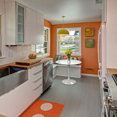 Mid-century modern kitchen photo in Minneapolis with a farmhouse sink, flat-panel cabinets, white cabinets, wood countertops, white backsplash and stainless steel appliances