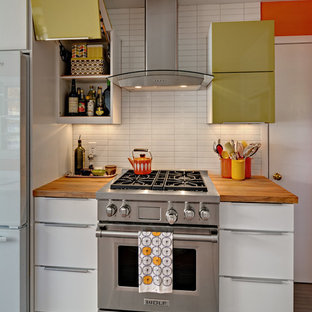 Small midcentury u-shaped separate kitchen in Minneapolis with a farmhouse sink, flat-panel cabinets, white cabinets, wood benchtops, white splashback, ceramic splashback, stainless steel appliances, linoleum floors and no island.