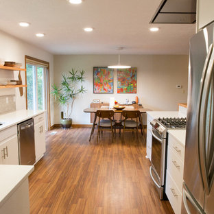 This is an example of a mid-sized midcentury galley open plan kitchen in Other with an undermount sink, flat-panel cabinets, white cabinets, quartzite benchtops, grey splashback, porcelain splashback, stainless steel appliances, vinyl floors and a peninsula.